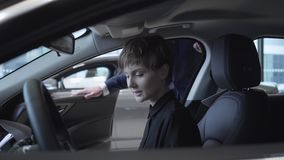 La mujer joven examina el nuevo auto mientras que se sienta en el compartimiento de pasajero del nuevo coche en la sala de exposi almacen de metraje de vídeo