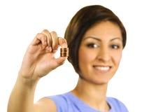 La mujer joven exprime una pila de peniques. Fotos de archivo libres de regalías