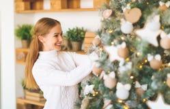 La mujer joven feliz adorna en el árbol de navidad Foto de archivo