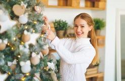 La mujer joven feliz adorna en el árbol de navidad Fotos de archivo libres de regalías
