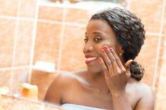 La mujer joven feliz aplica la crema en su cara Fotografía de archivo