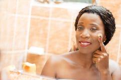 La mujer joven feliz aplica la crema en su cara Foto de archivo