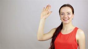 La mujer joven feliz cambia y saluda la sonrisa waving almacen de metraje de vídeo