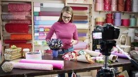 La mujer joven feliz como florista en una floristería diseña y crea arreglos de flores en las guirnaldas, ramos, floreros almacen de metraje de vídeo