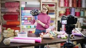 La mujer joven feliz como florista en una floristería diseña y crea arreglos de flores en las guirnaldas, ramos, floreros metrajes