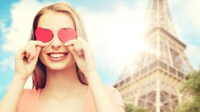 La mujer joven feliz con el corazón rojo forma en ojos Fotografía de archivo