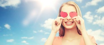 La mujer joven feliz con el corazón rojo forma en ojos Imagenes de archivo