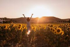 La mujer joven feliz con los brazos se abrió de su parte posterior en un campo del girasol en la puesta del sol foto de archivo libre de regalías