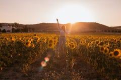 La mujer joven feliz con los brazos se abrió en un campo del girasol en la puesta del sol imágenes de archivo libres de regalías