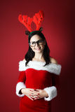 La mujer joven feliz con traje y Papá Noel del reno viste en fondo rojo Fotografía de archivo libre de regalías