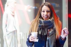 La mujer joven feliz con una taza de té caliente en invierno camina al aire libre Imagenes de archivo