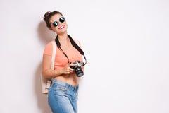 La mujer joven feliz del inconformista en vidrios sostiene la cámara retra de la foto Imágenes de archivo libres de regalías