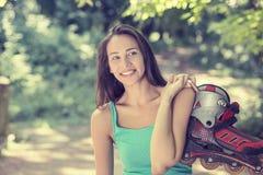 La mujer joven feliz del retrato que va rollerblading sostenerse en línea patina foto de archivo