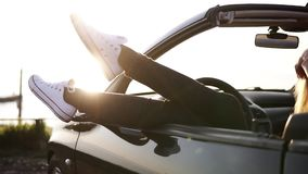 La mujer joven feliz descansa y empuja sus zapatillas de deporte blancas del coche coloreado negro convertible Sol suave del vera almacen de video