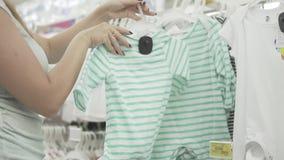 La mujer joven feliz elige la ropa para sus niños Mujer hermosa en la tienda que intenta la calidad de la ropa metrajes