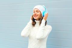 La mujer joven feliz en auriculares goza escucha la música que lleva un sombrero hecho punto, suéter sobre azul Imágenes de archivo libres de regalías