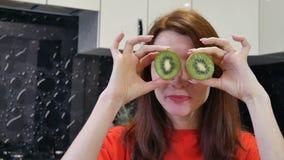 La mujer joven feliz en camisa roja muestra pedazos frescos de kiwi mientras que cocina la comida vegetariana en la cocina almacen de metraje de vídeo