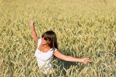 La mujer joven feliz en campo de maíz disfruta de puesta del sol Fotografía de archivo libre de regalías