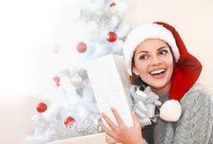 La mujer joven feliz en el sombrero de Papá Noel disfruta en el regalo al lado del árbol de navidad Imagen de archivo