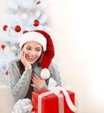 La mujer joven feliz en el sombrero de Papá Noel disfruta en el regalo al lado del árbol de navidad Fotografía de archivo libre de regalías