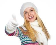 La mujer joven feliz en invierno viste mostrar los pulgares para arriba Fotos de archivo libres de regalías