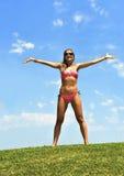 La mujer joven feliz en la abertura del bikini arma al aire en cielo del verano Imagen de archivo