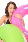 La mujer joven feliz en la tenencia del día de fiesta infló los anillos de goma Foto de archivo libre de regalías