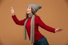 La mujer joven feliz en rojo hizo punto el suéter y el sombrero gris que planteaban el ove Imagen de archivo libre de regalías