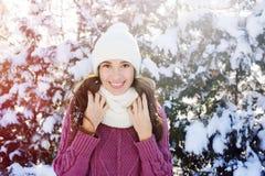 La mujer joven feliz en un blanco hizo punto el sombrero y la bufanda en parque del invierno Imagenes de archivo