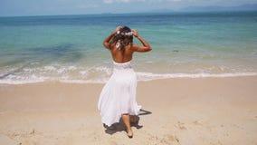 La mujer joven feliz en una guirnalda blanca del vestido y de la flor corre al mar descalzo y se goza las manos de los aumentos P almacen de video