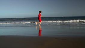 La mujer joven feliz en vestido rojo corre a lo largo de la playa del océano en la puesta del sol Concepto de vida moderna despre almacen de video