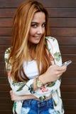 La mujer joven feliz envía el mensaje de texto en su teléfono móvil mientras que se coloca en fondo de madera de la pared Imagen de archivo libre de regalías