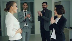 La mujer joven feliz está consiguiendo trabajo en compañía después de entrevista acertada y está sacudiendo las manos con el enca almacen de metraje de vídeo