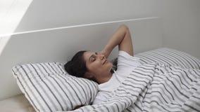 La mujer joven feliz está despertando en su dormitorio en la madrugada, mirando para arriba almacen de metraje de vídeo