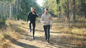 La mujer joven feliz está haciendo deportes con su novio hermoso que salta en parque en la trayectoria y que ríe disfrutando de l metrajes