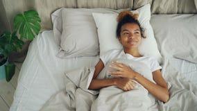 La mujer joven feliz está mintiendo en la cama despierta y está sonriendo disfrutando de vida despreocupada, de la cama cómoda y  almacen de metraje de vídeo