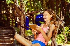La mujer joven feliz está riendo mientras que mira a su ou del cojín de la tableta Fotos de archivo