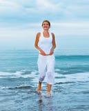 La mujer joven feliz está saltando en la playa Fotos de archivo