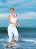 La mujer joven feliz está saltando en la playa Foto de archivo libre de regalías