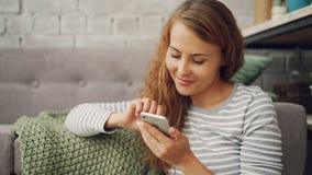 La mujer joven feliz está sosteniendo la pantalla táctil del smartphone y sonriendo comprobando medios sociales considere o leyen metrajes