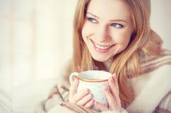La mujer joven feliz está debajo de una manta y de una taza de café el mañana del invierno en casa Foto de archivo