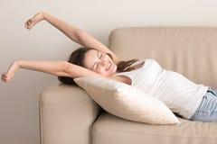 La mujer joven feliz estira en el sofá después de siesta Fotos de archivo libres de regalías