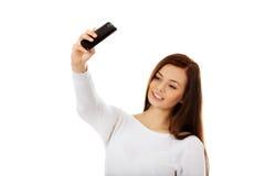 La mujer joven feliz hace selfies con el teléfono elegante Imagen de archivo libre de regalías