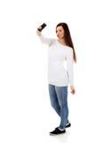 La mujer joven feliz hace selfies con el teléfono elegante Fotografía de archivo