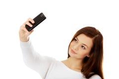 La mujer joven feliz hace selfies con el teléfono elegante Imágenes de archivo libres de regalías