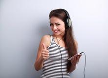 La mujer joven feliz hermosa escucha la música que sostiene el teléfono a Imagenes de archivo