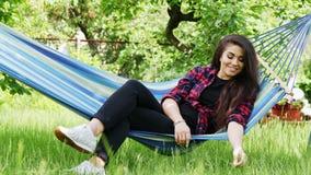 La mujer joven feliz hermosa miente en una hamaca en el jardín, sonríe y se relaja almacen de video