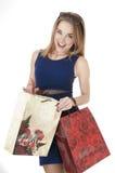 La mujer joven feliz hermosa que sostiene el regalo de las compras empaqueta. Foto de archivo