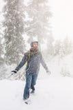 La mujer joven feliz juega con una nieve al aire libre Foto de archivo libre de regalías