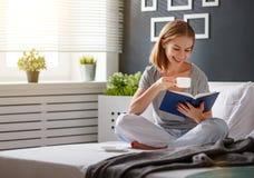 La mujer joven feliz lee el libro y bebe el café en cama foto de archivo